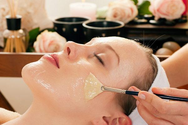 Dùng chổi trang điểm để thấm dầu dừa và thoa đều lên toàn bộ khuôn mặt